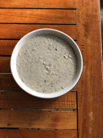 A full bowl of cream of mushroom soup on a wooden table